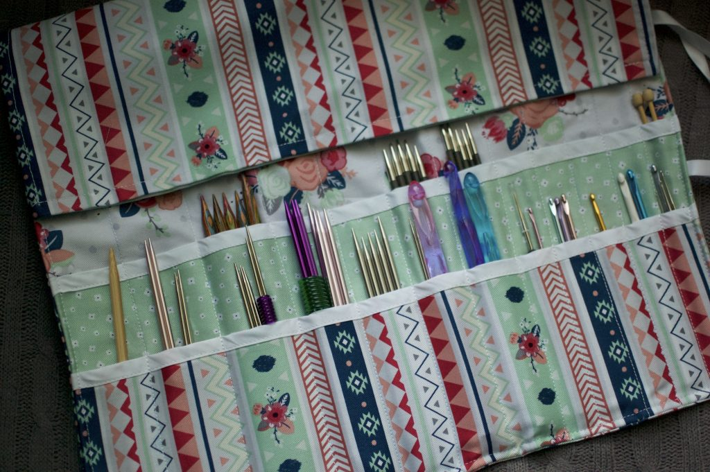 Knitting needles and crochet hooks in a holder made by Carly